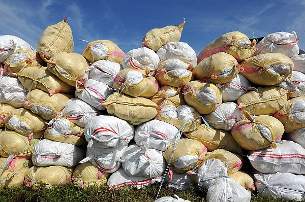 100-pound sacks of rice are stacked before being loaded into U.S. Navy helicopters assigned to the Ronald Reagan Carrier Strike Group for delivery to remote locations on the Philippine Island of Panay.