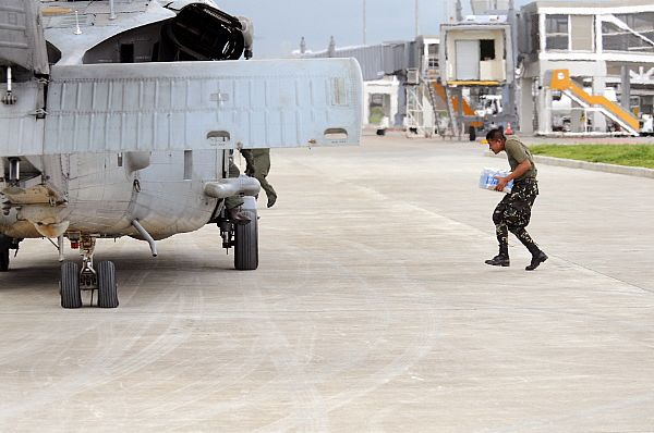A member of the Philippine Army carries bottled water to a waiting helicopter assigned to Helicopter Anti-Submarine Squadron (HS) 4 at Iloilo airport. The U.S. Navy and the Philippine Army and Air Force have been working side by side during disaster relief in the wake of Typhoon Fengshen.
