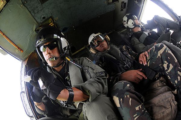 A service member with the Armed Forces of the Philippines sits with a U.S. Navy aircrew in the aft station of an SH-60F Seahawk assigned Helicopter Anti-Submarine Squadron (HS) 4 during a humanitarian mission on the Philippine island of Panay. HS-4 is embarked aboard the aircraft carrier USS Ronald Reagan (CVN 76).