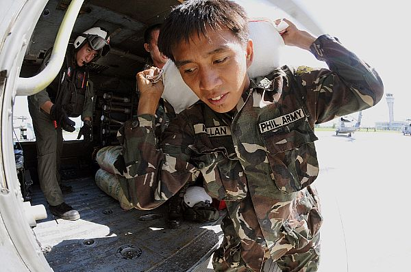A soldier from the Armed Forces of the Philippines carries a 100-pound bag of rice to a helicopter assigned to the