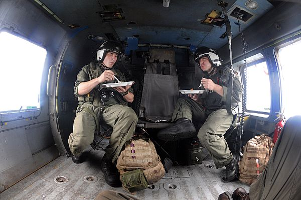 Air crews assigned to Helicopter Anti-Submarine Squadron (HS) 4 have been working long hours for five days delivering food and water to Panay Island, Republic of the Philippines in the wake of Typhoon Fengshen. From left, Aviation Warfare Systems Operator Justin Irwin, 23, Pleasant Hill, Mo, and Aviation Warfare Systems Operator Jeremy Thomas, 27, Warren, Ohio, grab a quick meal between refueling and airlift missions.