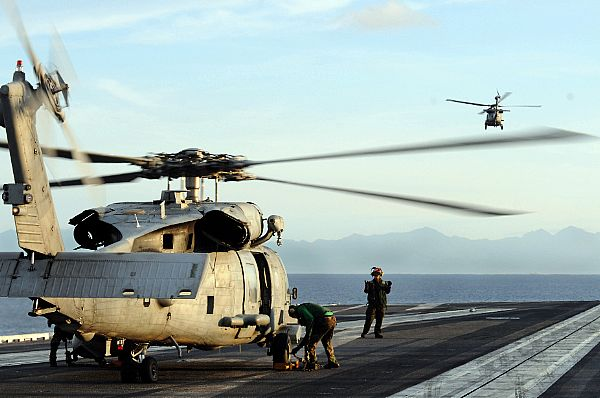 An SH-60F Seahawk flies off in the distance as crewmen and maintenance crews assigned to Helicopter Anti-Submarine Squadron (HS) 4 prepare a second helicopter for launch from the aircraft carrier USS Ronald Reagan (CVN 76) during humanitarian operations on Panay Island, Philippines.