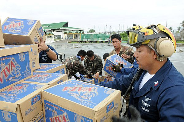 Aviation Boatswains Mate (Handler) 2nd Class William Sum unloads bottled water during relief efforts in wake of Typhoon Fengshen. Petty Officer Sum, a native of Panorama City, Calif., is assigned to USS Ronald Reagan (CVN 76) and is ashore at the Kalibo Airport directing U.S. helicopters arriving with supplies.
