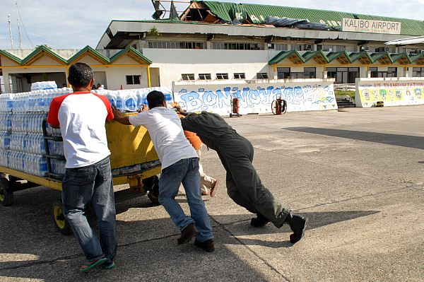 Aviation Structural Mechanic 2nd Class Myron Robertson, of Carson, Calif., helps local Philippine residents push a cart full of supplies at Kalibo Airport. The supplies, delivered by the