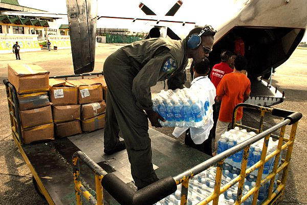 Aviation Structural Mechanic 2nd Class Myron Robertson, of Carson, Calif., stacks supplies onto a cart at Kalibo Airport while a C-2A Greyhound is unloaded. The supplies, delivered by the