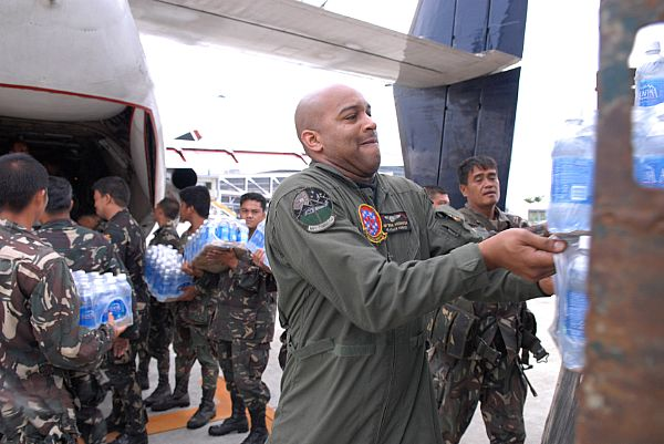 Aviation Warfare Systems Operator 1st Class Brian Anderson, of Spartanburg, S.C., helps service members assigned to the Philippine Army load a C-2A Greyhound with supplies from the Nimitz-class aircraft carrier USS Ronald Reagan (CVN 76) at Iloilo Airport. The supplies will be transferred to Kalibo Airport to be distributed to those in need after the wake of Typhoon Fengshen.