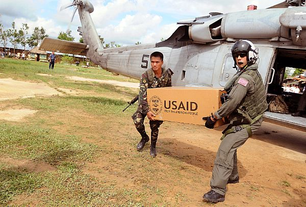 Aviation Warfare Systems Operator 2nd Class Anthony Chavez, a native of San Bernardino, Calif., works with a soldier from the Armed forces of the Philippines to move relief supplies to a school on the Panay Island.