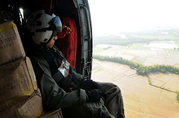 Aviation Warfare Systems Operator 2nd Class Anthony Chavez, of San Bernardino, Calif., looks over flooded areas in the Republic of the Philippines caused by Typhoon Fengshen. Riding in an SH-60F Seahawk assigned to the