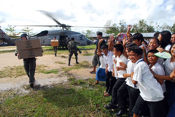 Aviation Warfare Systems Operator 2nd Class Jeremy Thomas, a native of Warren, Ohio, carries supplies to local citizens of Balasan, Philippines. Thomas is a helicopter crewman with the
