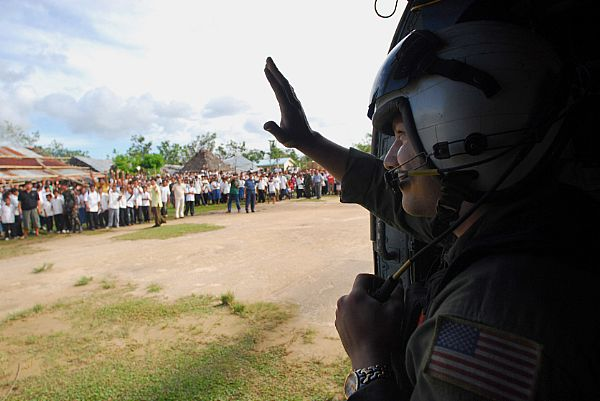 Aviation Warfare Systems Operator 2nd Class Jeremy Thomas, a native of Warren, Ohio, waves to citizens of the Municipality of Balasan, Philippines after delivering hygiene items, water and tents to the remote city. Thomas is a helicopter crewman with the