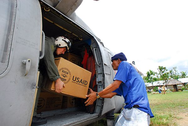 Aviation Warfare Systems Operator 2nd Class Justin Irwin, a native of Pleasant Hill, Mo., hands a citizen from the Municipality of Balasan, Philippines a box of humanitarian relief supplies. Irwin is a helicopter crewman with the