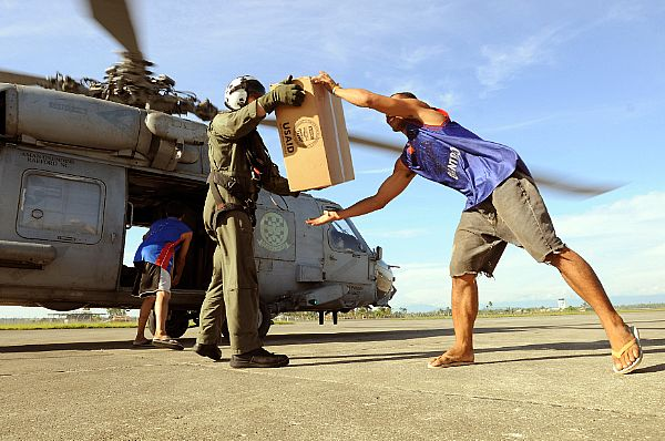 Aviation Warfare Systems Operator 2nd Class Slavek Glownia and a villager from Kalibo move a box of humanitarian supplies from an SH-60F Seahawk flown by members of Helicopter Anti-Submarine Squadron (HS) 4.