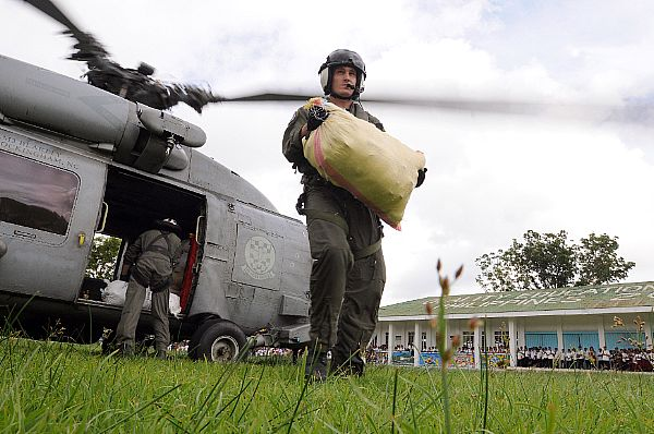 Aviation Warfare Systems Operator 2nd Class Travis Story, a native of Reading, Calif., carries a 100-pound sack of rice to a school in the remote village of Altavas. Story is a helicopter pilot with the