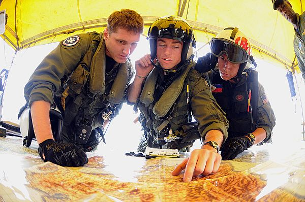 Aviation Warfare Systems Operator 2nd Class Travis Story, a native of Reading, Calif., left, Lt. Brandon Sheets, a native of Abilene, Texas, and Aviation Warfare Systems Operator 2nd Class Keith Holt, a native of the Philippines, look over a map during a mission briefing at Iloilo Airport before their next mission to remote locations on Panay Island that were hardest hit by Typhoon Fengshen.