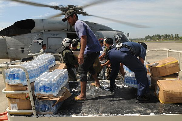 Bottles of water transported from the Nimitz-class aircraft carrier USS Ronald Reagan (CVN 76) are unloaded by Armed Forces of the Philippines (AFP), U.S. Navy personnel and civilians. The supplies will be distributed throughout devastated areas caused by Typhoon Fengshen.