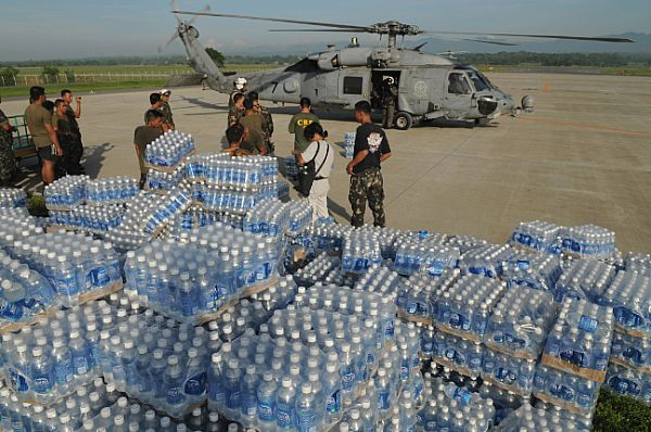 Bottles of water transported from the Nimitz-class aircraft carrier USS Ronald Reagan (CVN 76) wait to be delivered to devastated areas in the Republic of the Philippines caused by Typhoon Fengshen after Armed Forces of the Philippines (AFP) and U.S. Navy personnel unloaded it from an SH-60F Seahawk assigned to the