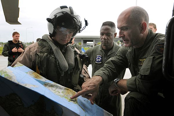 Capt. Thomas P. Lalor, right, deputy commander, Carrier Air Wing (CVW) 14, gives Lt. Ralph Silvas directions to the area he is to deliver humanitarian supplies to on Panay Island. Lalor is coordinating air operations for the Ronald Reagan Carrier Strike Group while they assist the Republic of the Philippines in the wake of Typhoon Fengshen.