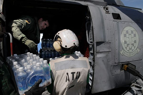 Chief Aviation Warfare Systems Operator Andrew Smith, of New Castle, Del., helps load water onto an SH-60F Seahawk