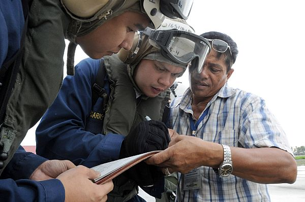 Chief Storekeeper Jep Rosario, Storekeeper 1st Class Lorenz Partosan and a villager from Kalibo begin to organize how they will receive thousands of liters of bottled water during a vertical replenishment from the Military Sealift Command combat stores ship USNS Niagara Falls (T-AFS 3). Roasario and Partosan, assigned to the aircraft carrier USS Ronald Reagan (CVN 76), are both from the Philippines.