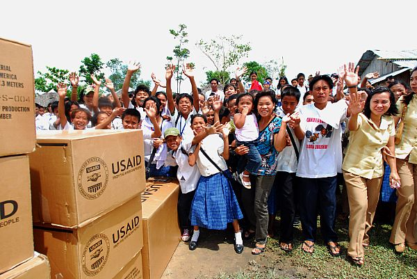 Citizens from the Municipality of Balasan, Philippines wave after receiving supplies from air crewmen assigned to the