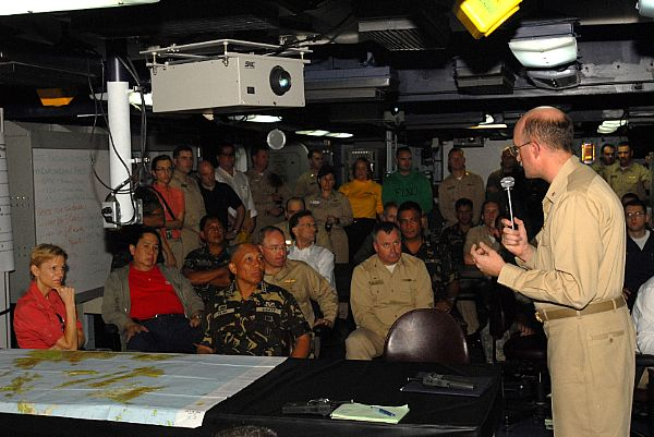 Cmdr. Paige, USS Ronald Reagan's Intelligence Officer gives a brief to Armed Forces of the Philippines, Chief of Staff, Gen. Alexander B. Yano and U.S. Ambassador to the Philippines Kristie Kenney