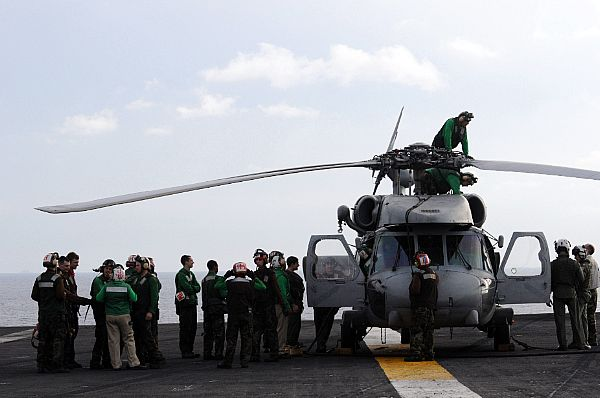 Flight deck personnel stand by as last minute maintenance is performed on an SH-60F Seahawk assigned to the