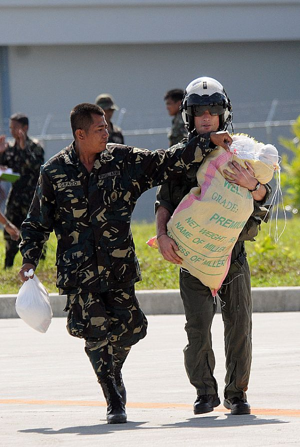 Lt. Brandon Sheets, right, carries a 100-pound sack of rice while a soldier from the Armed Forces of the Philippines lends a hand trying to keep the bag closed. The rice will be delivered to the remote location of Binglusan on the island of Panay.