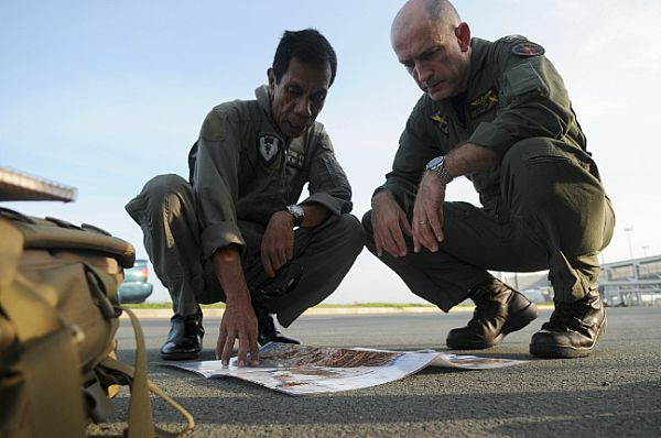 Lt. Col. Oscar Lasangue, the civil relations commander of Armed Forces of the Philippines (AFP), Central Command, left, and Capt. Thomas P. Lalor, deputy commander of Carrier Air Wing (CVW) 14, discuss the flight route for the delivery of food and water from the Nimitz-class aircraft carrier USS Ronald Reagan (CVN 76) to devastated areas in the Republic of the Philippines caused by Typhoon Fengshen.