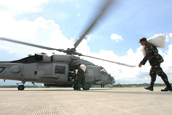 Members of the Armed Forces of the Phillipines (AFP) load an HH-60H Seahawk assigned to the