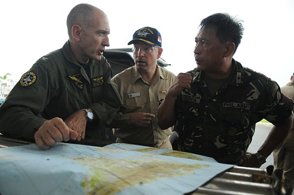 Rear Adm. James P. Wisecup, commander, Carrier Strike Group (CSG) 7, center, Brig. Gen. Jorge Segovia, deputy assistant chief of staff for Operations of Armed Forces Philippines (AFP), right, and Capt. Thomas P. Lalor, deputy commander of Carrier Air Wing (CVW) 14, discuss the current relief efforts of the Nimitz-class aircraft carrier USS Ronald Reagan (CVN 76).