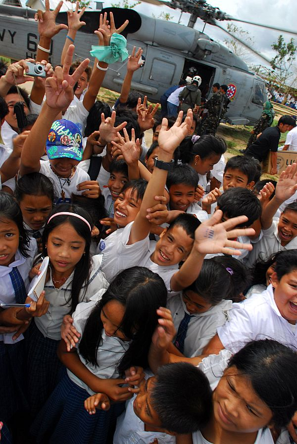 Residents from the Municipality of Balasan, Philippines wave and cheer after Sailors assigned to the