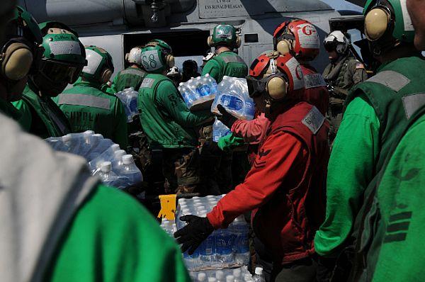 Sailors aboard the Nimitz-class aircraft carrier USS Ronald Reagan (CVN 76) load bottles of water onto an SH-60F Seahawk
