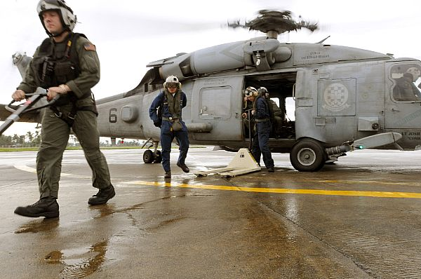 Sailors from the Ronald Reagan Carrier Group debark an HH-60H Seahawk assigned to Helicopter Anti-Submarine Squadron (HS) 4 while delivering bottled water to hard hit areas of the region following Typhoon Fengshen.