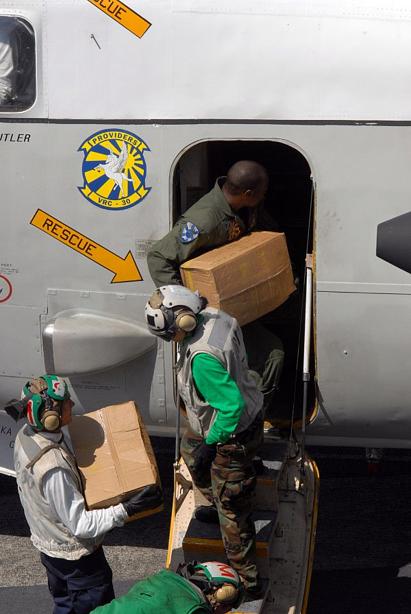 Sailors load cases of water bound for the Philippines onto a C-2A Greyhound