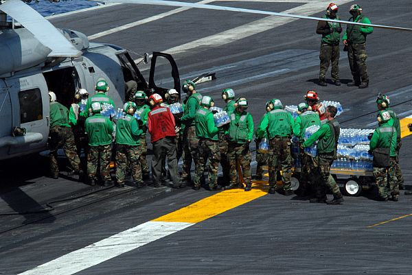 Sailors load cases of water bound for the Philippines onto an HH-60H helicopter