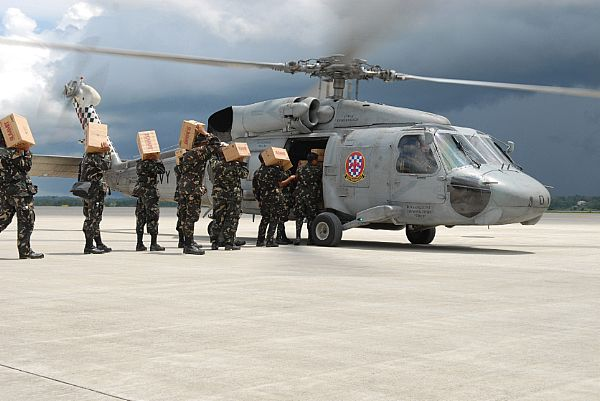 Service members assigned to the Philippine Army load an SH-60 Seahawk assigned to the