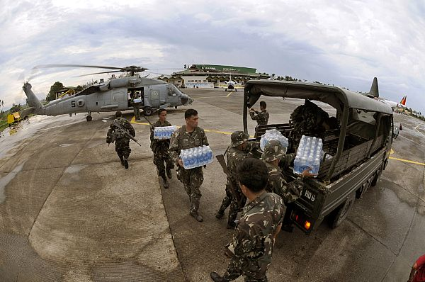 Servicemen from the United States Navy and the Philippine Army work together unloading much needed supplies for people suffering in the wake of Typhoon Fengshen at Kalibo Airport.