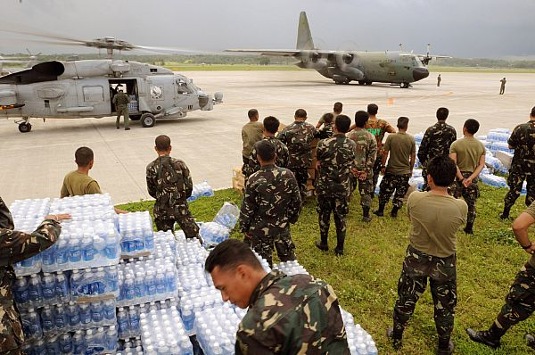 Servicemen of the Philippine Army stage themselves to transport bottled water to aircrafts assigned to the U.S. Navy and the Republic of the Philippines Air Force. The U.S. Navy and the Philippine Army and Air Force have been working side by side during disaster relief in the wake of Typhoon Fengshen.