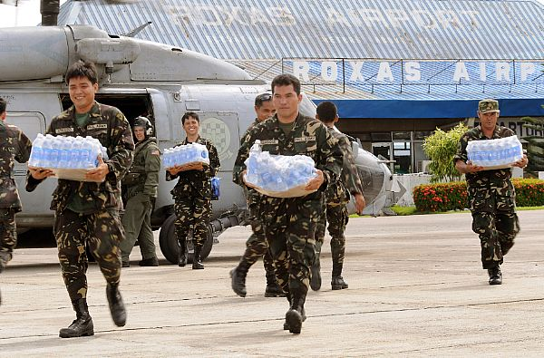 Servicemen of the Philippine Army transport bottled water from an SH-60 helicopter