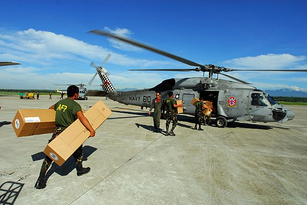 Soldiers with the Armed Forces of the Philippines carry relief supplies to a waiting SH-60F Seahawk assigned to Helicopter Anti-Submarine Squadron (HS) 4 for delivery to remote locations on the island of Panay, Philippines. Tents, hygiene items and water are to be dropped off in the Municipality of Balasan, which was hit hard by Typhoon Fengshen.