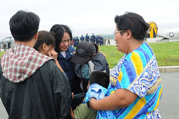 Storekeeper Seaman Grace Geroche, a native of Iloilo and Sailor assigned to the Nimitz-class aircraft carrier USS Ronald Reagan (CVN 76), embraces family members upon arriving as part of U.S. Navy relief operations. Her family nearly lost their lives in flooding caused by Typhoon Fengshen.