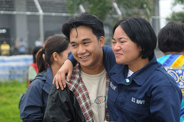 Storekeeper Seaman Grace Geroche, a native of Iloilo and Sailor assigned to the Nimitz-class aircraft carrier USS Ronald Reagan (CVN 76), embraces her brother upon arriving as part of U.S. Navy relief operations. Her family nearly lost their lives in flooding caused by Typhoon Fengshen.