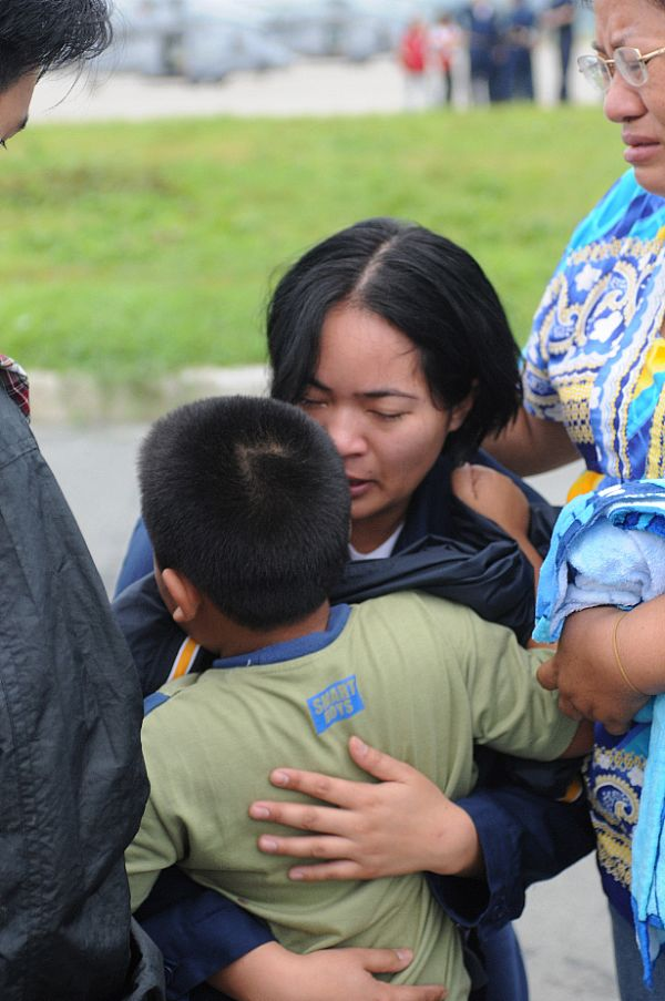 Storekeeper Seaman Grace Geroche, a native of Iloilo and Sailor assigned to the Nimitz-class aircraft carrier USS Ronald Reagan (CVN 76), embraces her younger brother upon arriving as part of U.S. Navy relief operations. Her family nearly lost their lives in flooding caused by Typhoon Fengshen.