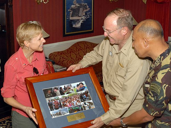 U.S. Ambassador to the Philippines, Kristie A. Kenney is presented with a collection of photos depicting relief efforts by USS Ronald Reagan (CVN 76), and other ships in her group