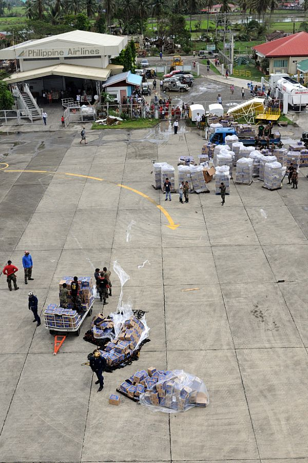 U.S. Navy and Philippine Army servicemen working together with their Philippine counterparts at the Kalibo Airport to get water and supplies to people affected by Typhoon Fengshen.